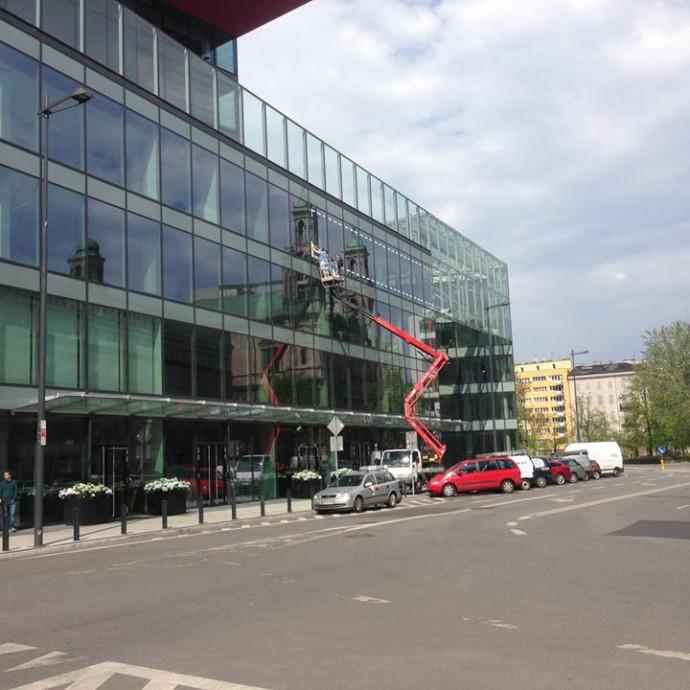 Wyklejanie z użyciem podnośnika koszowego folii na elewacji wysokościowca Cosmopolitan w Warszawie